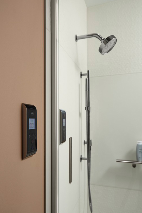 Contemporary bathroom shower featuring digital controls, a showerhead and handshower.