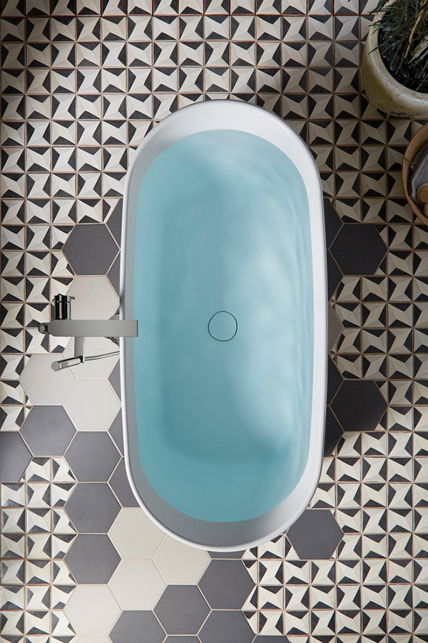 Bird's eye view of simple oval freestanding bath on geometric floor tile pattern